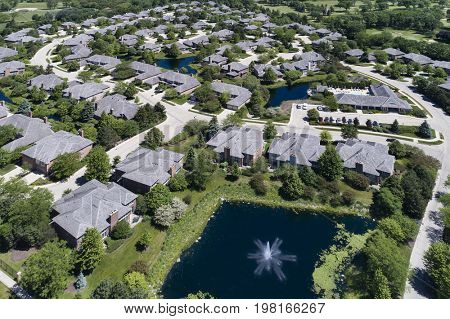 Aerial view of a luxury townhouse complex with ponds in a Chicago suburban neighborhood in summer.