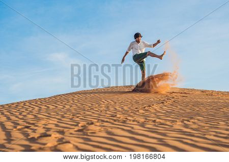 A Man Is Kicking Sand In A Red Desert. Splash Of Anger Concept