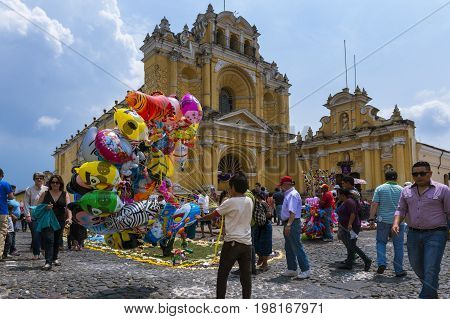 Antigua Guatemala - April 17 2014: Young boy selling balloons in a street of the old city of Antigua with the San Pedro Hospital on the background in Guatemala