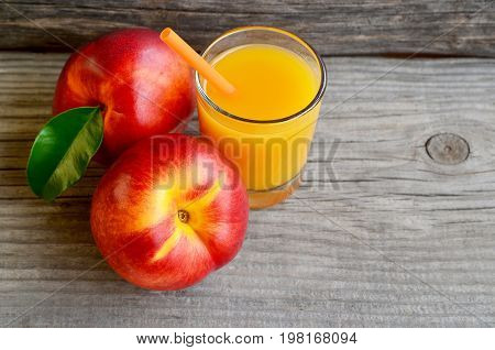 Fresh ripe organic nectarines and a glass of juice on old wooden table.Nectarine juice.Peach juice.Diet,healthy food,raw food concept.Selective focus.