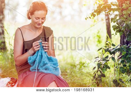 A dark-haired young woman in a romantic light top and a wide skirt knits a blue and blue mohair thread sweater sitting in a birch forest on a sunny summer day knitting with knitting needles