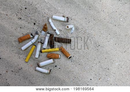 The cigarette butts on the sand by the beach.