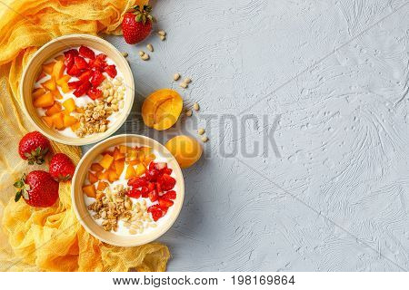 Natural yoghurt with pieces of apricots, strawberries, granola and pine nuts in two bowls on light background. Top view with place for text