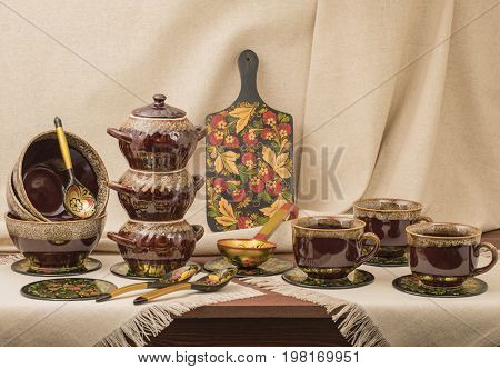 Clay pots for cooking with cups and boards on a table with a background
