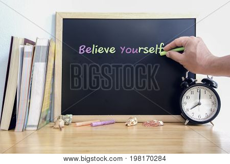 Wooden table and blackboard with writing Believe Yourself