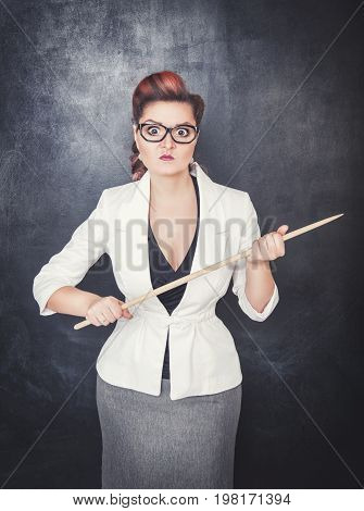 Serious Woman Teacher Pointing Out On Blackboard Background