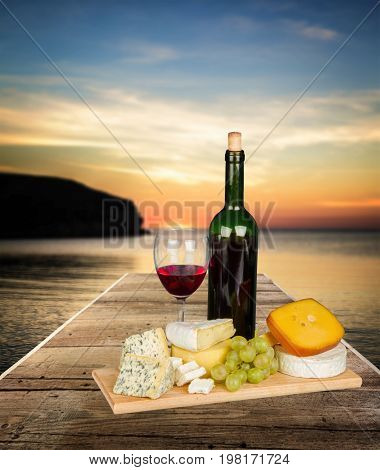 Red wine cheese grapes color background glass
