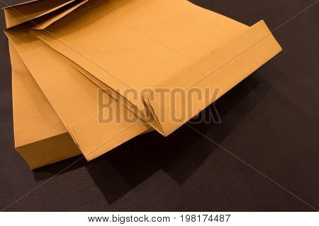 Blank Envelopes On A Dark Leatherette Background Texture. Back Side Of Yellow Envelopes On Dark Brow
