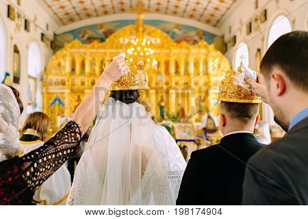 The Witnesses Of The Newlyweds Hold The Golden Crowns In The Church Over The Heads Of The Bride And