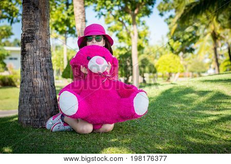 Girl Hugging A Teddy Bear Happily On The Grass Under The Coconut.