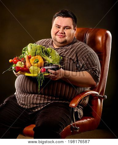 Diet fat man eating healthy food with vegetables for overweight male. Male trying to lose weight first time. Hungry person ready to eat everything. Choice between healthy harmful nutrition.