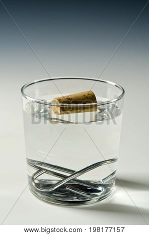 Physics. A cork floats in water and metal objets sinks. Archimedes principle.