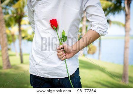 Man Holding Roses Behind.