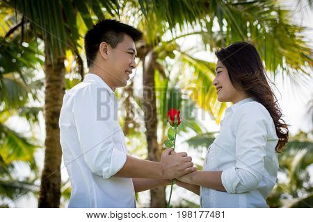 Beautiful Young Couple With White Coats Standing On A Green Lawn. Man Giving Red Roses To Young Wome