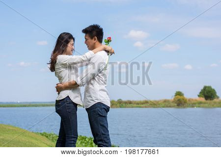 Beautiful Young Couple With White Coats Standing On A Green Lawn. Man Hugging Young Woman Holding A