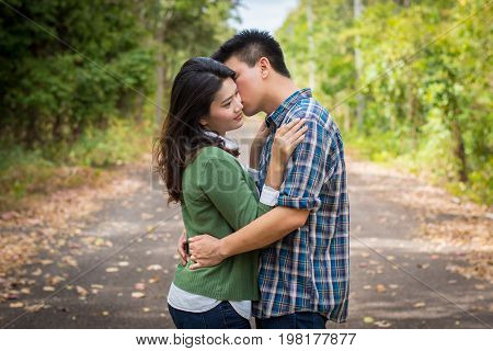 Young Man Kiss Young Woman On A Forest Road.