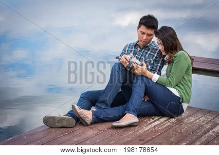Young Men And Young Women Couple Together Sitting On Bench Waterfront Port In The Park. Handle Vinta