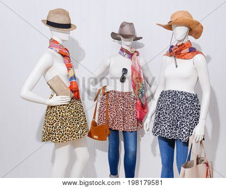 female clothing with hat and bag ,scarf, sunglasses on three mannequin
