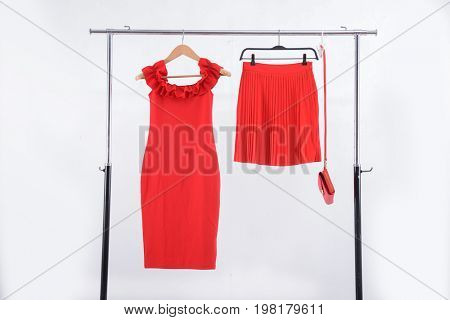 Red flared skirt ,bag, sundress on clothes rack isolated