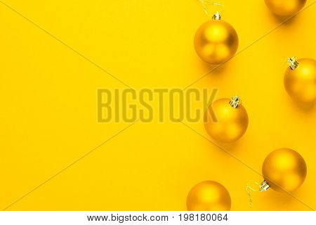 Christmas tree decoration balls. christmas decoration on yellow background. cristmas decoration balls with copy space. top view of yellow cristmas decoration balls over yellow background