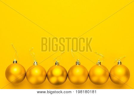 Christmas tree decoration balls in a row. christmas decoration on yellow background. cristmas decoration balls with copy space. top view of yellow cristmas decoration balls over yellow background