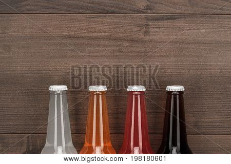 glass bottles of different sweet drinks. various glass bottles on brown table. glass bottles of different sweet drinks on the wooden background. glass bottles of different sweet drinks in order