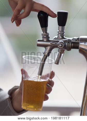 Barman pours beer into a plastic glass .