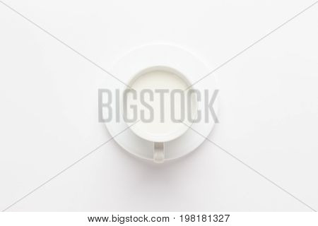 cup of milk on white background. cup of milk not isolated. cup of milk view from above. top view of white cup of milk for healthy breakfast