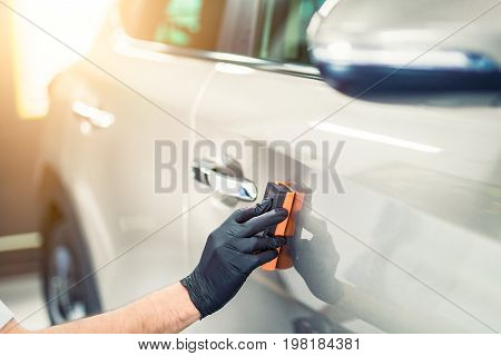 Car detailing - Man applies nano protective coating to the car. Selective focus.