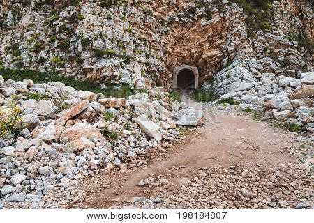 Entrance to the mountain tunnel on the way from Perazica Do to Petrovac, Montenegro. Wild rocks and stones on the path threw the mountain.