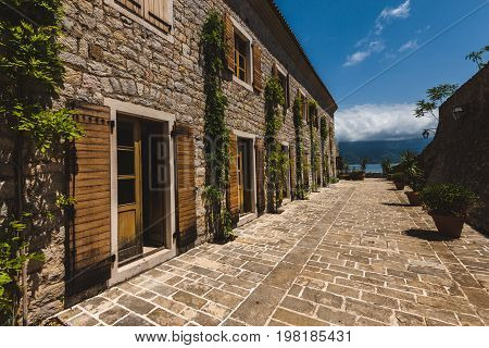 Traditional barrack building in Citadela complex in Budva, Montenegro. Ancient stone house with shattered windows and green ivy in Budva Old Town by sunny day.