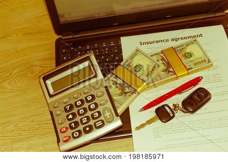Car insurance form with car keys pen much dollars Laptop and calculator on the table. Insurance concept - Retro color