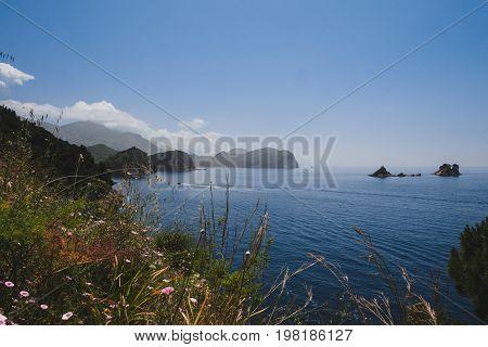 Shoreline and Adriatic sea scenic landscape on the coast path to Petrovac, Montenegro. Rocks, water and Sveta Nedjelja island by sunset on the way from Perazica Do to Petrovac near Rezevici village.