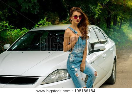 young gorgeous women in glasses sexy sits on a white car
