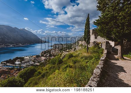 Kotor Bay and Old Town view from above Kotor's castle of San Giovanni walls. Mountains, traditional house roofs, stone frotress and Boka Kotorska fjord wide angle view.