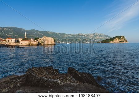 Budva Old town, St.John church spire, mountains, St. Nicholas island and Adriatic sea panoramic landscape. Tourist capital Budva wide angle view by golden hour.