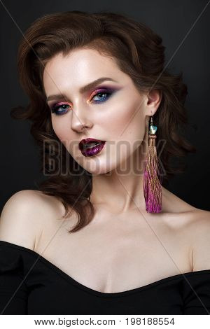 Portrait of beautiful young woman with professional makeup, perfect skin, wavy hair, long earrings. Trendy colorful smoky eyes.