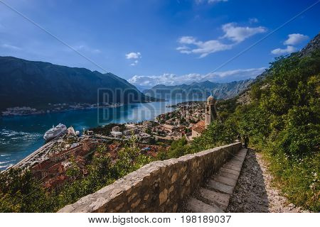 Kotor Bay and Old Town view from above Kotor's castle of San Giovanni. Stone staircase on Kotor fortress, traditional house roofs, cathedral dome and Boka Kotorska wide angle view. Montenegro.