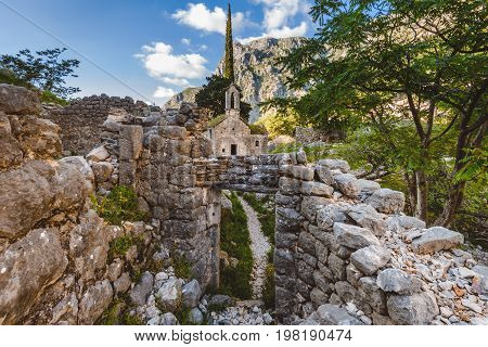 Ancient Serbian church, city ruins and mountain valley landscape near Kotor castle in Montenegro. Old mountain church and monastery in Kotor region near path to Lovchen mountain. Saint Ivan chapel.