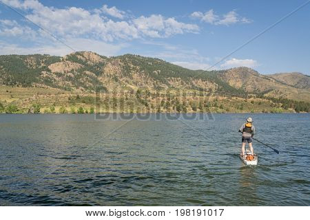 paddling stand up paddleboard on mountain lake in northern Colorado, summer scenery at Horsetooth Reservoir near Fort Collins