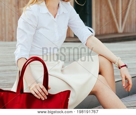 Part of body. Girl sitting on the stairs with a big red super fashionable handbag in a dress and Wide Fit Pointed Heels on a warm summer evening. Fashion. Bag. Close up. Outdoor.