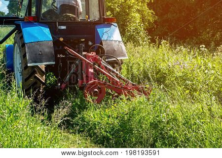 Farm tractor green mowing high grass in a Sunny summer day. Close-up. The horizontal frame.