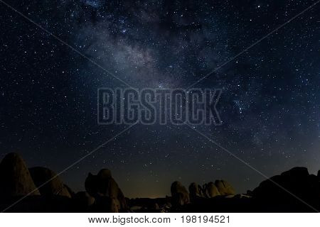 Milky Way southeastern sky with boulders bottom quarter of frame