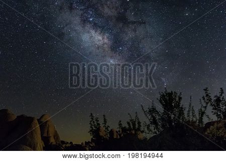 Milky Way over desert boulders and brush with a meteor streak