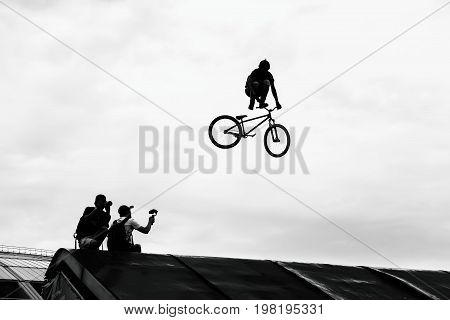 Extrem Sport. BMX bike jumping in the sky on high speed, black and white silhouette.