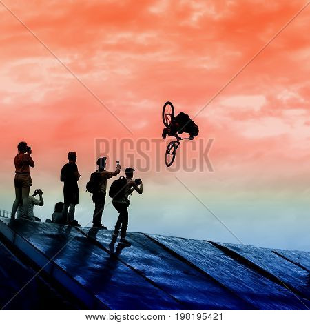 Extrem Sport and risk. Silhouette of a Young man doing a jump with a bmx bike against bright sky. Several photographers make shooting high on trampoline