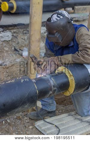 Welder Welding Underground Steel Pipe Kneels On Ground 3