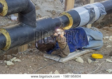 Welder Welding Underground Steel Pipe Lying On Ground 3