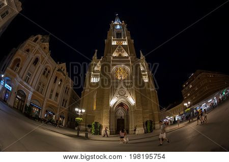 NOVI SAD SERBIA - JULY 30 2017: Night view of the Liberty Square (Trg. Slobode) with Mary Church tourists and old buildings. One of the cities designated as the European capital of culture in 2021.