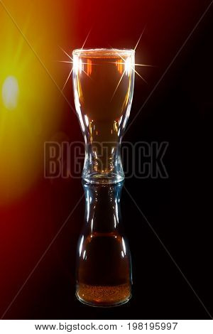 Award winning beer under spotlight. Lager drink in a bottle shaped pint glass for International Beer Day. Against black background with spotlight and lens flare.